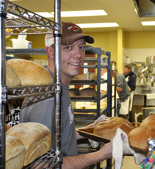 Baker Photo. He is pulling a tray of hot whole wheat bread out of the oven and smiling.