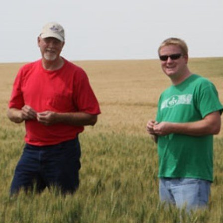 This is a photo of a wheat farmer and a Great Harvest wheat manager in a wheat field.