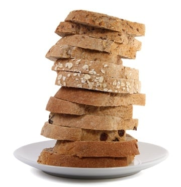 Photo of hand sliced whole grain slices of bread stacked on top of each other on a white plate
