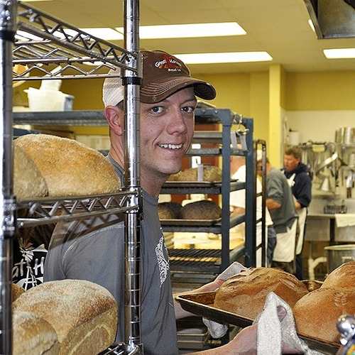 great harvest employee smiling and pulling loafs out of the oven
