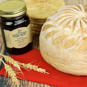 A photo of a honey whole wheat round unsliced loaf, a jar of jam, a stack of cookies, on a red napkin with a wheat stalk