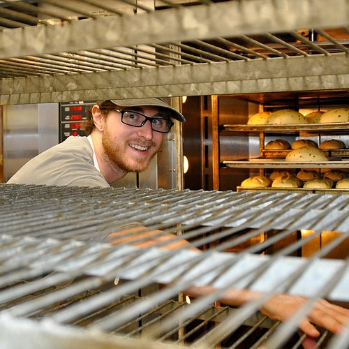 great harvest team member grabbing bread out of an oven